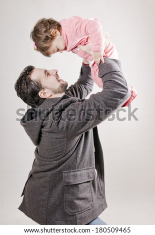 Isolated father lifting little girl up to the air - stock photo