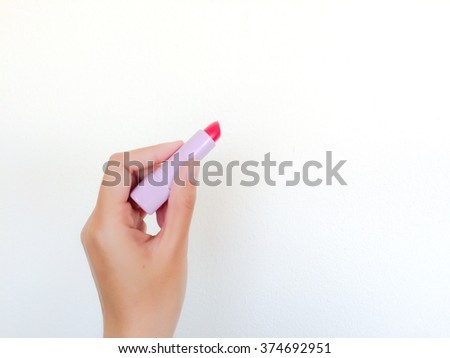 isolated female hand hold red lipstick in Light Purple tube on white wall - stock photo