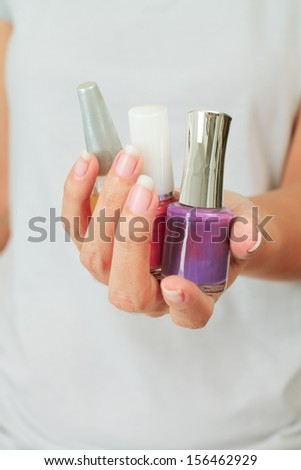 Isolated Female hand with nail varnish bottles - stock photo