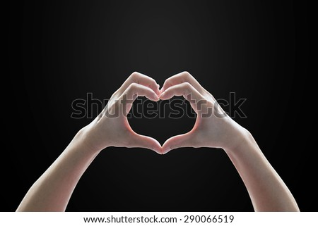 Isolated female human hands in heart shape on black background: Universal hand sign language meaning love and caring      - stock photo