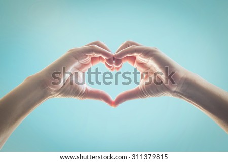 Isolated female human hands in heart shape raising against clear bright blue sky background in vintage style color tone: Universal hand sign language expression meaning love, caring, friendship, trust - stock photo