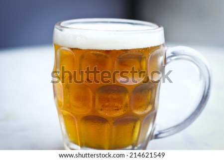 Isolated full cold beer jar on white table and blue wall.