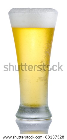 Isolated full length portrait of a full cold beer in pilsner style glass with head above rim level and partial reflection