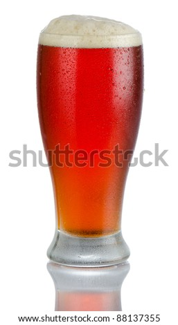 Isolated full length portrait of a full cold beer in tumbler style glass with head above rim level and partial reflection