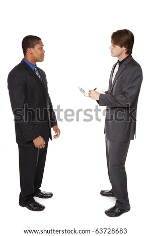 Isolated full length studio shot of a businessman answering a survey performed by another businessman.