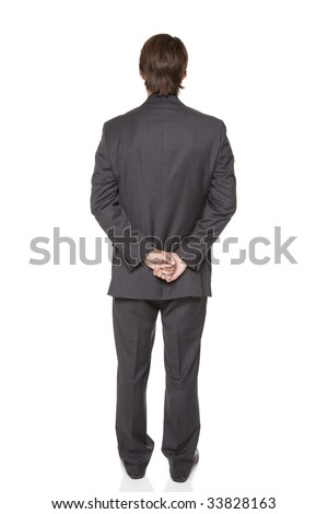 Isolated full length studio shot of a businessman facing away from the camera with his hands clasped. - stock photo