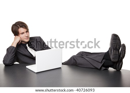Isolated full length studio shot of a businessman kicking his heels up and working on his laptop while relaxing at a conference table. - stock photo