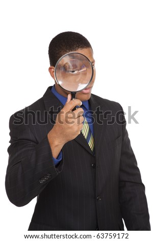 Isolated full length studio shot of a businessman looking at the camera through a magnifying glass. - stock photo