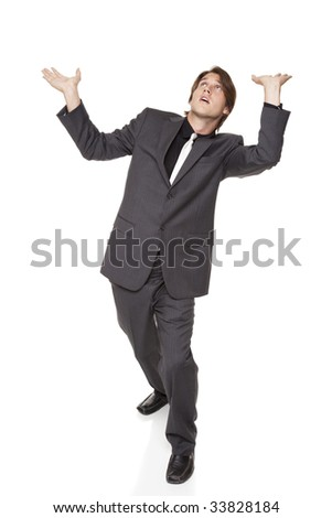 Isolated full length studio shot of a businessman posed as if he were supporting a large weight over his head. - stock photo