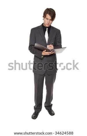 Isolated full length studio shot of a businessman standing and writing in a notebook he is holding.
