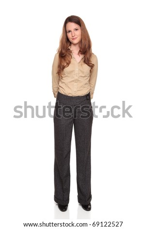 Isolated full length studio shot of a Caucasian businesswoman smiling and looking at the camera with her hands clasped behind her.