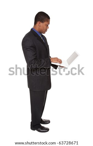 Isolated full length studio shot of a confident businessman looking at a laptop he is holding. - stock photo