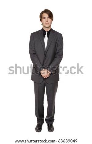 Isolated full length studio shot of a confident businessman looking at the camera with his hands clasped. - stock photo