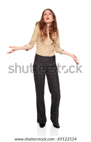 Isolated full length studio shot of the front view of a Caucasian businesswoman looking up in disbelief with arms raised.