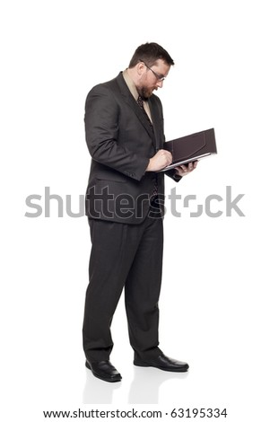 Isolated full length studio shot of the side view of a businessman writing on a notepad.