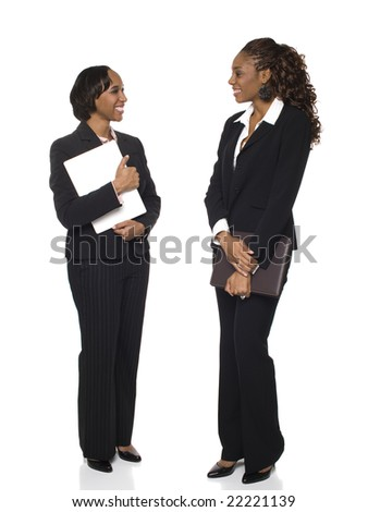 Isolated full length studio shot of two happy businesswomen talking to each other. - stock photo