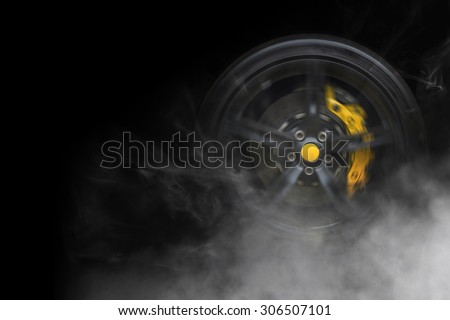 Isolated generic sport car wheel with yellow breaks drifting and smoking on a black background - stock photo