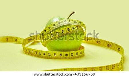 Isolated green apple with a measuring tape on a yellow background - stock photo