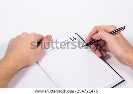 isolated hand holding pen and writing in diary - stock photo