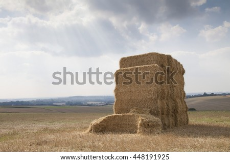 Isolated hay bale on agricultural farmland on the South Downs in Hampshire, England, United Kingdom with sun rays, clouds and a moody sky.