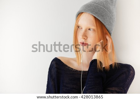 Isolated headshot of attractive hipster young female listening to her favorite music with earphones. Student girl wearing headphones looking away with thoughtful and dreamy expression on her face   - stock photo