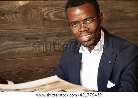 Isolated headshot of happy successful African American entrepreneur in spectacles and suit looking and smiling at the camera with confident cheerful expression against wooden wall background - stock photo