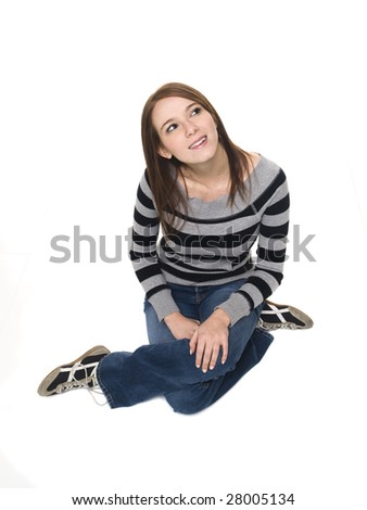 Isolated high angle studio shot of a casually dressed young adult woman sitting and looking up at an angle. - stock photo