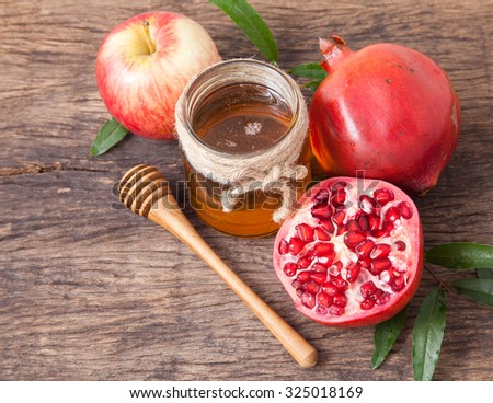 Isolated honey, apple and pomegranate for traditional holiday symbols rosh hashanah (jewesh holiday) on wooden table top and wooden background - stock photo