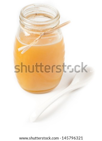 Isolated honey jar and spoon with shadow