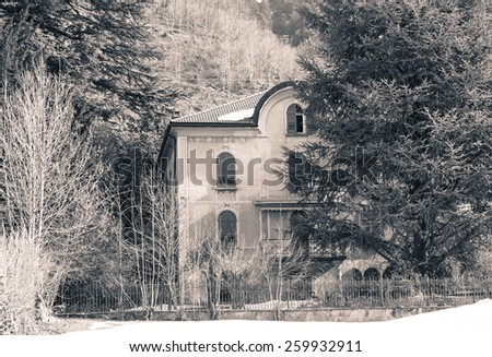 isolated house in the woods seems abandoned, like in a horror movie - stock photo