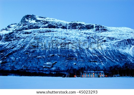 Isolated house on the bottom of mountain in Norway - stock photo