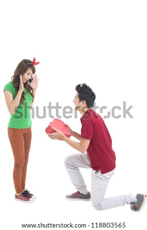 Isolated image of a guy presenting his girlfriend with a heart-shaped giftbox, conceptual shot, good for Valentine'??s Day - stock photo