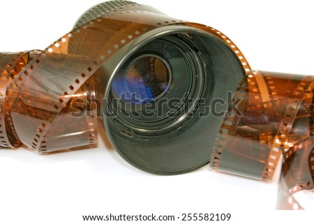 Isolated image of a lens and photographic film closeup - stock photo