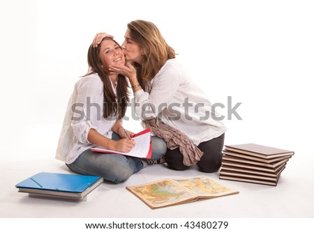 Isolated image of a mother kissing her teenage daughter - stock photo