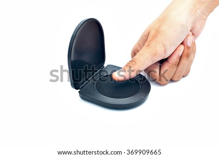 Isolated image of a thumb getting inked using a thumb print ink pad. - stock photo