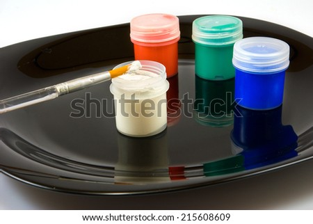 Isolated image of different paints and brush on a black plate - stock photo