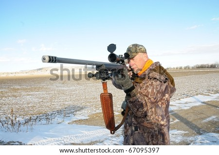 Isolated image of hunter with rifle.  Image taken while on hunting exhibition in Wyoming. - stock photo