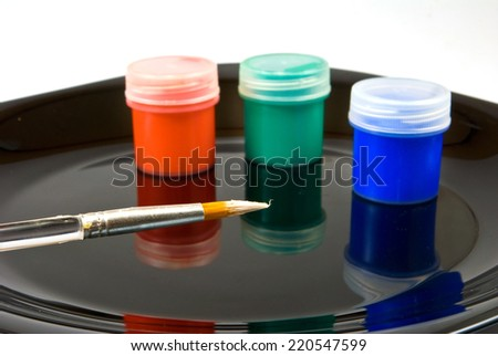 Isolated image of paints and brush on a black plate - stock photo