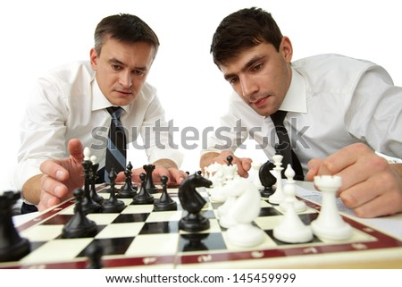 Isolated image of serious businessmen developing their strategic thinking by playing chess - stock photo