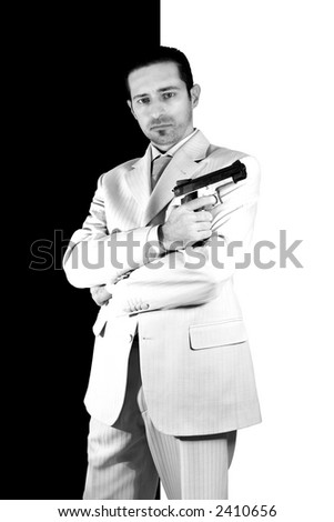 Isolated Mafia with arms crossed and a gun on hand - stock photo
