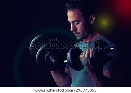 Isolated male working out with weights. Low-key lighting with black background and spotlights. - stock photo