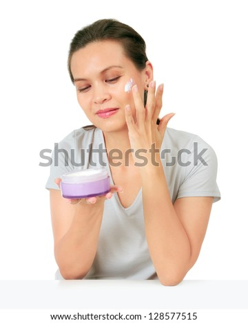 Isolated Middle Age Asian Woman applies cream on her face. - stock photo