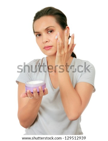 Isolated Middle Age Asian Woman appllies cream on her face. - stock photo