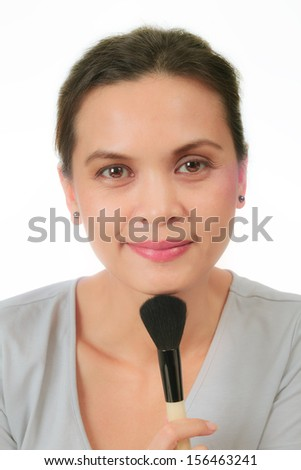 Isolated middle age asian woman with make up brush. - stock photo