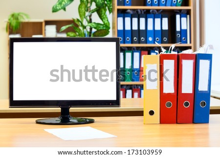 Isolated monitor screen and colored folders for papers on the table - stock photo