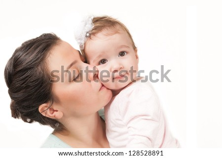 Isolated mother kissing her baby girl on white background