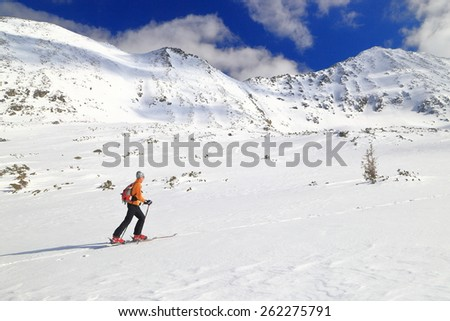 Isolated mountaineer climbs on touring skies on sunny snow covered slope - stock photo