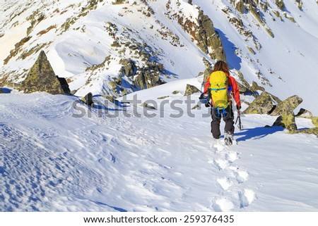 Isolated mountaineer leaving foot steps on snow covered ridge in winter - stock photo