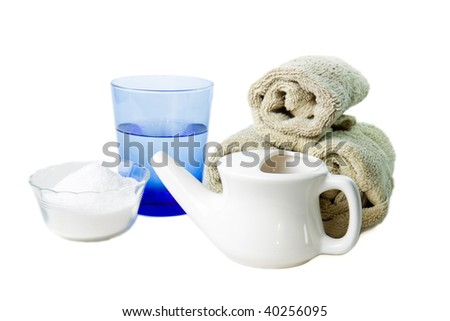 Isolated Neti Pot, used for clearing the nasal passages, shown with a glass of water and salt - stock photo