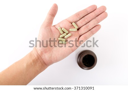 Isolated of Hand holding a pill capsule with a bottle. - stock photo